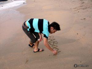 Таец пишет слово на песке